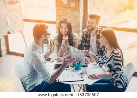 Cheerful Partners Are Discussing An Idea Of New Start-up By Smiling And Enjoying Each Others Company