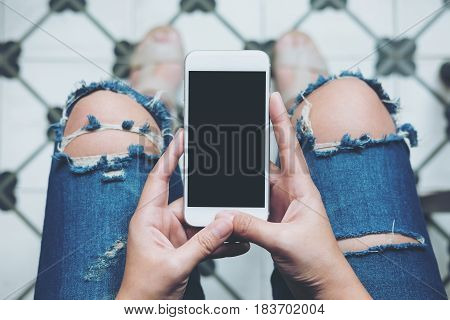 Mockup image of hand holding white mobile phone with blank black screen on leg with a vintage tile floor in cafe feeling relax