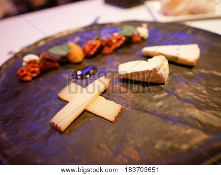 Mini-Size Cheese Platter served on a brown color plate in fine dining restaurant.
