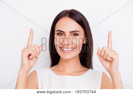 Close Up Portrait Of Young Cheerful Pretty Girl Gesturing Up With Her Fingers. She Is Smiling, Stand