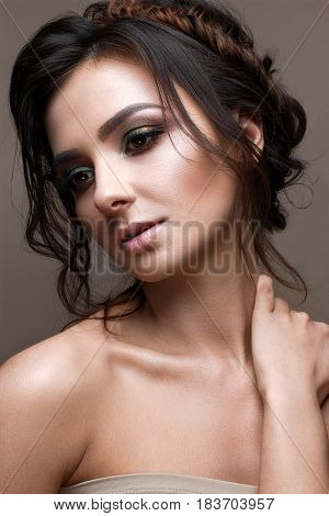 A young girl with bright creative makeup and evening hairstyle. Beautiful model with perfect skin. Beauty of the face. Photo is taken in the studio.