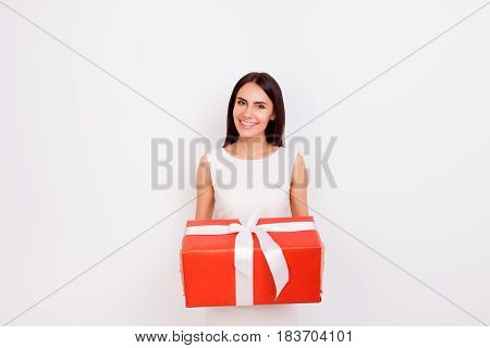 Happy Smiling Cute Woman Holding Big Red Present Box On White Background. She Is Smiling, Dressed In