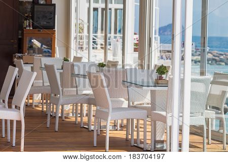 Modern cafe interior with white furniture, Liguria, Italy