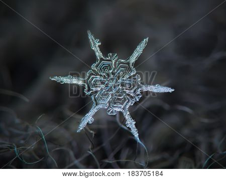 Real snowflake macro photo: snow crystal with unusual structure - simple, narrow and straight arms, and big hexagonal center, formed by six broad sectors with beautiful inner pattern.