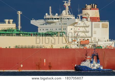 GAS CARRIER - Great ship and small tugboat in the sun
