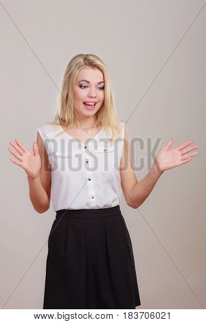 Shrugging woman in doubt doing shrug attractive confused girl gesturing do not know sign on gray background
