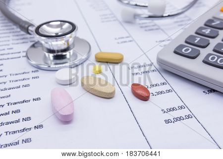 Stethoscope and medicine on bank statements background concept financial health.