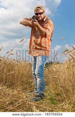 Hunter at cap and sunglasses aiming a gun at field