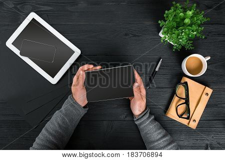 Directly above view of human hands with digital tablet. Digital tablet, diary, coffee cup and potted plant on work desk. Man working from home.