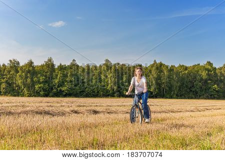 Matured woman on biycle at sloping rye field