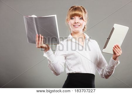 Woman learning with ebook reader and book. Choice between modern educational technology and traditional way method. Girl holding digital tablet pc and textbook. Contemporary education.
