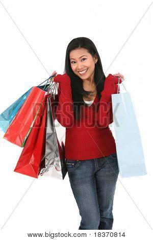 happy smiling female shopper holding shopping bags on isolated background