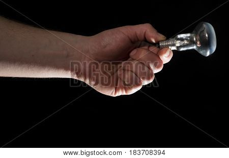 Man's hand holding electrical lamp on black background