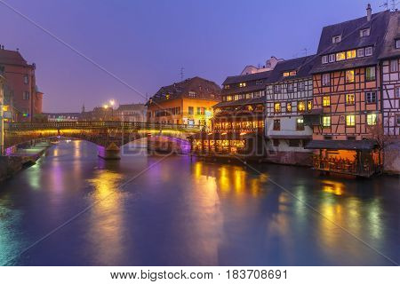 Traditional Alsatian half-timbered houses and bridge in Petite France during twilight blue hour, Strasbourg, Alsace, France