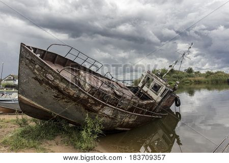 View on old rusty boat lays on lakeshore