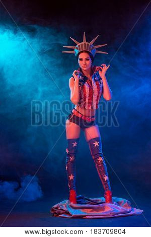Young woman in stage costume of striptease dancer posing. Sexy woman in a statue of America costume