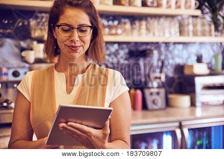 Mature Lady Working In Coffee Shop