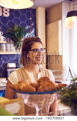 Smiling Lady Behind Plate Of Croissants