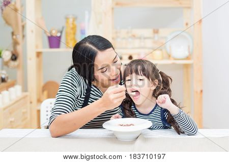 Asian young mother feeding breakfast for her daughter with a kitchen background.