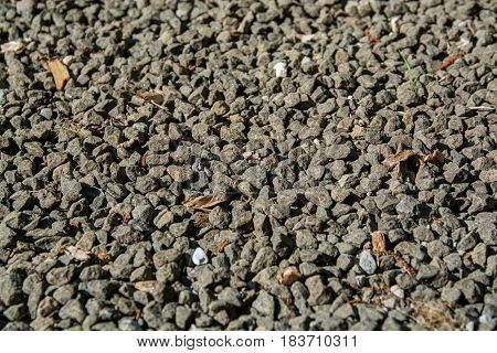 gravel background grey gravel rocks and some brown old leaves