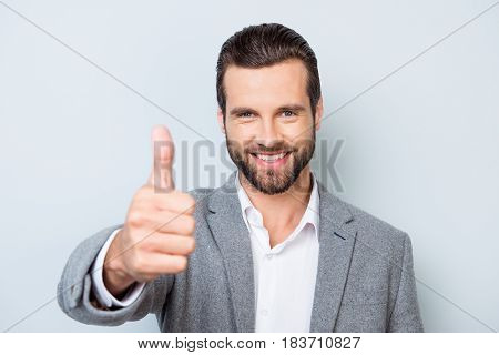 Young Smiling Handsome Worker In Formal Clothing Demonstrating Thumb Up Against Gray Background