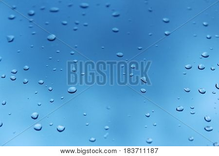 Raindrops on a window, blue sky in the background.