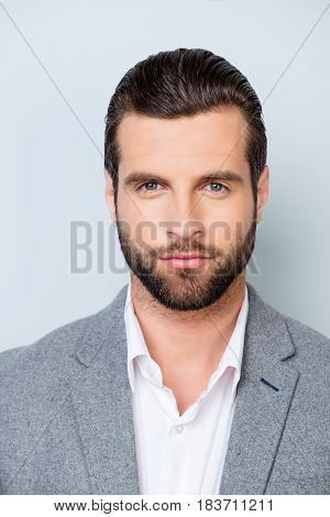 Vertical Close Up Portrait Of Serious Young Minded Man In White Shirt And Gray Jacket On Gray Backgr
