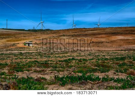 Power wind mills in the back of an agriculture field against hazy sky in Portugal.