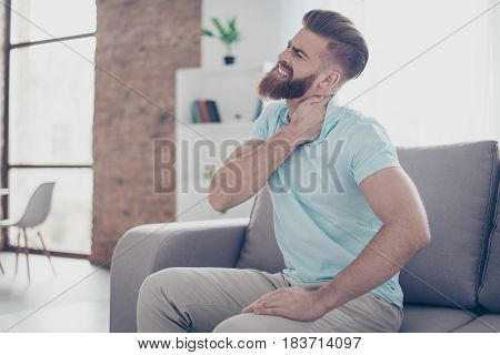 Young Frusytrated Man Is Having A Strong Pain In Neck. He Is At Home And Alone, Sitting On Sofa