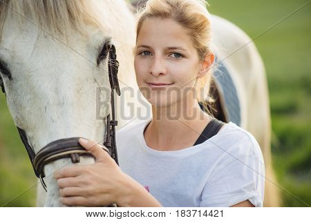 Young farmer woman portrait with her white horse