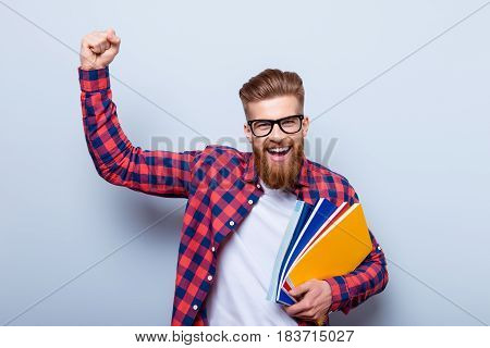 Young Cheerful Student In Glasses And In Checkered Shirt With Books In Hands Celebrating Ending Of E