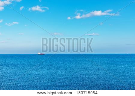 A View Of The Enormous Ocean, In The Distance A Flowing Ship, Beautiful Blue Sky In Contact With Cle