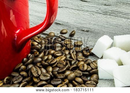 coffee grains with cup and sugar on grunge wooden background