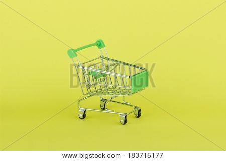 Empty Miniature Shopping Pushcart, Yellow Background