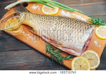 fresh fish carp carcass with lemon m rosemary on wooden background.
