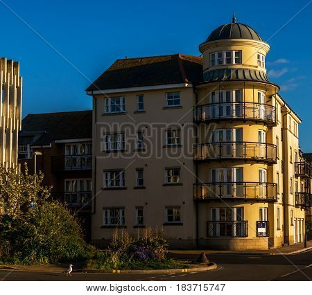 View Of A Tall Building On A Corner Of A Street In An English Town, Interesting Architecture