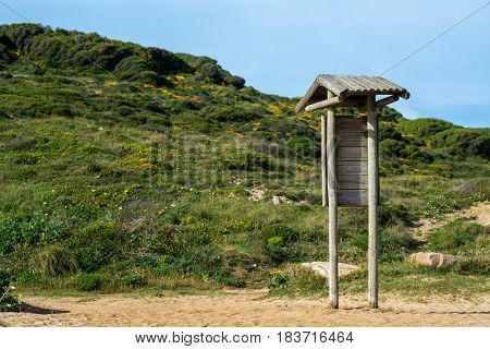 wood structure like little bus stop with green hill in the back