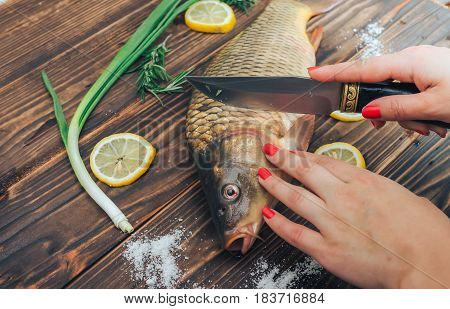 Cutting carp female hands on wooden background