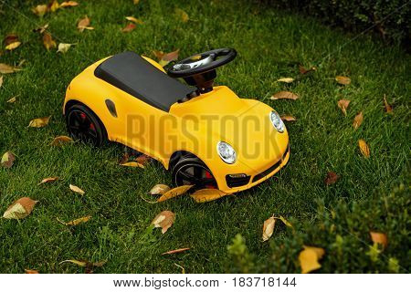 Cool yellow toy car for small child parked on a green grass in garden