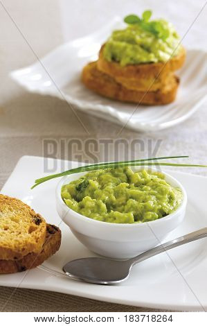 Guacamole on toast served on a table.