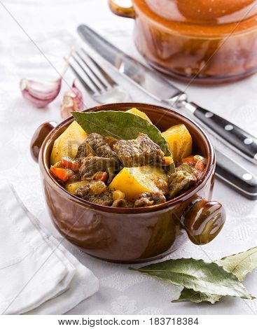 Traditional meat stew with potatoes and bay leaves in a cooking pot.