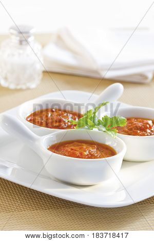 Three bowls of homemade tomato sauce served on a table.