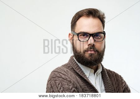 Closeup studio shot of positive young man with beard and glasses isolated on white