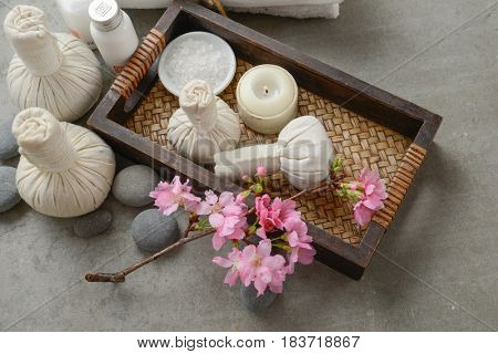 pink cherry flowers with candle, herbal ball in basket with towel,stones  on gray background