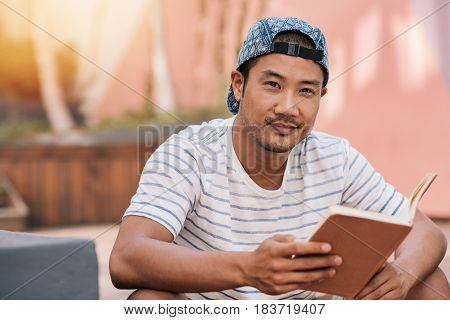 Portrait of a smiling young Asian man reading a novel while sitting alone on some stairs outside on a sunny day