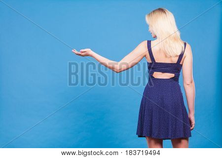 Woman wearing short navy dress pointing left with palm open hand at copyspace view from back.