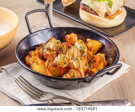 Patatas bravas spicy potatoes a typical Spanish dish with fried potato cubes and a spicy garlic sauce.
