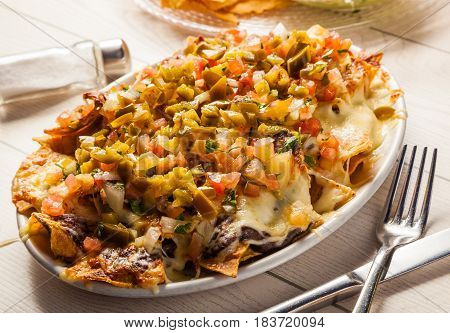 Mexican food: nachos with melted cheese tomato and jalapeno peppers.