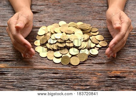 pile of gold coin with woman hand on the wooden background financial and saving concept.