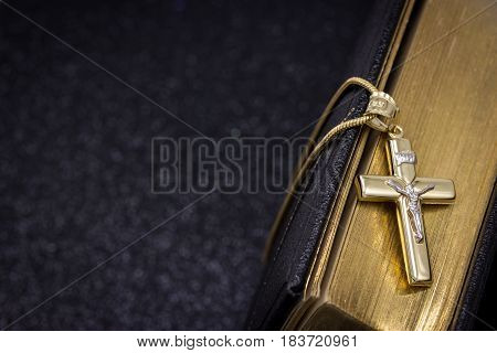 Gold cross and Bible on a black background
